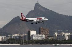 A TAM plane flies past the statue of Christ the Redeemer (in the background) as it prepares to land at Santos Dumont airport in Rio de Janeiro, Brazil, July 1, 2015. REUTERS/Sergio Moraes