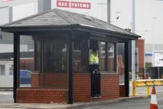 A security guard stands at the entrance to the naval dockyards, where BAE Systems is located, in Portsmouth, southern England November 6, 2013.  British defence contractor BAE Systems said it would start a consultation process to lay off 1,775 ship workers across the UK and would stop all shipbuilding at Portsmouth on the south coast of England next year.     REUTERS/Stefan Wermuth (BRITAIN - Tags: BUSINESS MILITARY POLITICS EMPLOYMENT) - RTX152FZ