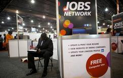 Una persona buscando trabajo completa un formulario en una feria de empleos en Filadelfia, 25 de julio de 2013. El número de estadounidenses que solicitaron por primera vez el seguro semanal por desempleo bajó la semana pasada al mínimo en más de 41 años y medio, sugiriendo que la expansión del empleo continuó sólida pese a desacelerarse en junio. REUTERS/Mark Makela