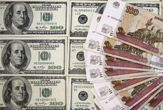 Рублевые и долларовые купюры в Сараево 9 марта 2015 года. Рубль в четверг умеренно снизился к доллару, обновив двухнедельные минимумы на фоне относительно дешевой нефти, а также из-за отсутствия крупных продаж экспортной выручки под уплату ключевых налогов следующей недели, на которые до сих пор надеется часть рынка.  REUTERS/Dado Ruvic