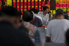 Investors look at computer screens in front of an electronic board showing stock information at a brokerage house in Shanghai, China, July 14, 2015. REUTERS/Aly Song