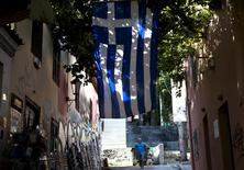 A souvenir shop owner cleans the sidewalk at the Plaka district under the Acropolis hill in Athens, Greece July 23, 2015. REUTERS/Ronen Zvulun