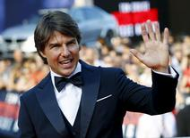 """Tom Cruise waves to fans upon his arrival for the world premiere of """"Mission Impossible - Rogue Nation"""" in front of State Opera house in Vienna, Austria, July 23, 2015. REUTERS/Leonhard Foeger"""