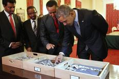 Dr. Zeresenay Alemseged Lemseged (2ndR), of the California Academy of Sciences,  directs U.S. President Barack Obama (R) to touch a fossilized vertebra of Lucy, an early human, before a State Dinner in Obama's honor at the National Palace in Addis Ababa, Ethiopia July 27, 2015. REUTERS/Jonathan Ernst