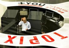 An employee looks at monitors at the Tokyo Stock Exchange (TSE) in Tokyo June 29, 2015. REUTERS/Thomas Peter