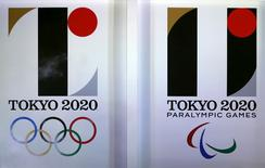Tokyo 2020 Olympic and Paralympic games emblems are seen as smoke rises during an unveiling event at Tokyo Metropolitan Government Building in Tokyo, Japan, July 24, 2015. REUTERS/Yuya Shino