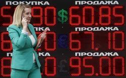 Женщина у табло с курсами обмена валюты в Москве. 28 июля 2015 года. Рубль утром пятницы дешевеет вслед за нефтью и в ожидании снижения ключевой ставки Банка России. В течение дня влияние на котировки будут оказывать также потоки дивидендного периода, а еще и фактор конца недели - с какими позициями или без них пожелают уйти на выходные участники рынка. REUTERS/Sergei Karpukhin