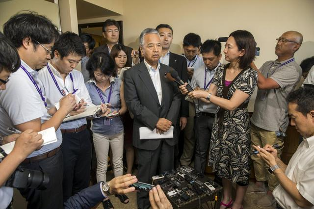 Japan's Economy Minister Akira Amari speaks at a news conference surrounded by Japanese press, at the Westin Resort in Lahaina, Maui, Hawaii July 30, 2015.  REUTERS/Marco Garcia
