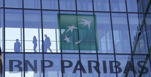 Personas caminan detrás del logo de BNP Paribas, en un edificio en Issy-les-Moulineaux, cerca de París, 23 de abril de 2015. El banco francés BNP Paribas reportó un aumento en sus ingresos de casi un 16 por ciento en el segundo trimestre, impulsado por unas operaciones bursátiles aceleradas, un dólar fuerte y unas empresas adquiridas recientemente. REUTERS/Gonzalo Fuentes