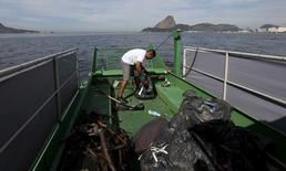 A worker inside a garbage-collecting boat collects the remains of garbage from the Guanabara Bay in Rio de Janeiro, Brazil, July 1, 2015. REUTERS/Sergio Moraes