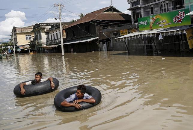 Men wade along a flooded street at Kalay township at Sagaing division, August 2, 2015.  REUTERS/Soe Zeya Tun