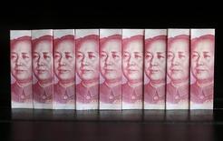Ilustración fotográfica realizada en Pekín de billetes de 100 yuanes. El Fondo Monetario Internacional debería postergar cualquier movimiento para sumar al yuan a su canasta de monedas denominada Derechos Especiales de Giro hasta septiembre del 2016, dijo un reporte del personal técnico del organismo, lo que podría terminar con las posibilidad de que la moneda china obtenga una inclusión anticipada. REUTERS/Jason Lee