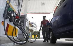 Un empleado carga combustible en una gasolinera de Shell en Viña del Mar, Chile, ene 12 2015. Tras reducir el gasto en 180.000 millones de dólares para enfrentar uno de los peores momentos de la industria en décadas, las petroleras aún desembolsan dinero y se endeudan más para mantener los dividendos a los accionistas.     REUTERS/Rodrigo Garrido