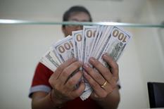 Bancário exibe notas de dólar norte-americano em Yangon, Mianmar, em julho. 17/07/2015 REUTERS/Soe Zeya Tun