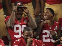 San Francisco 49ers outside linebacker Aldon Smith (99) jokes with teammate defensive back Chris Culliver (29) as they pose for a team picture during Media Day for the NFL's Super Bowl XLVII in New Orleans, Louisiana January 29, 2013. REUTERS/Sean Gardner