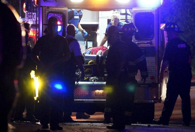 A black man is loaded into an ambulance after a police officer involved shooting in Ferguson, Missouri August 9, 2015. REUTERS/Rick Wilking