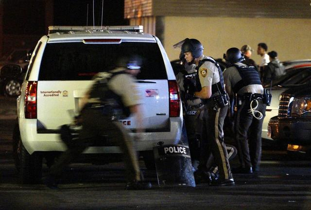 A police officer runs to take cover after shots were fired in a police-officer involved shooting in Ferguson, Missouri August 9, 2015. REUTERS/Rick Wilking