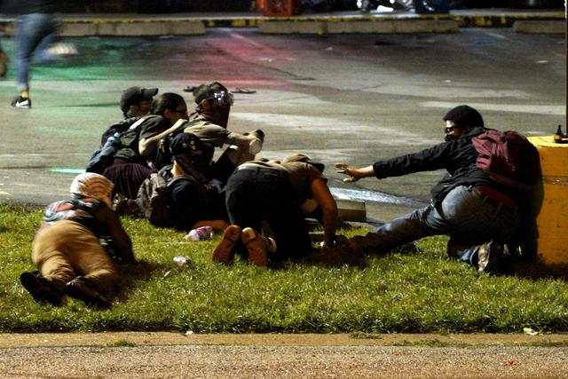 Protesters fall to the ground to take cover after shots were fired in a police-officer involved shooting in Ferguson, Missouri August 9, 2015. REUTERS/Rick Wilking