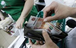 Женщина вынимает рублевую купюру из кошелька в Красноярске 6 августа 2015 года. Рубль утром вторника в минусе, отражая снижение нефти и валют-аналогов рубля, а также укрепление доллара США после новостей о девальвации китайского юаня. Дальнейшая динамика российской валюты продолжит копировать поведение нефтяного рынка, в ход торгов могут вмешиваться внутренние денежные потоки, связанные с дивидендами. REUTERS/Ilya Naymushin