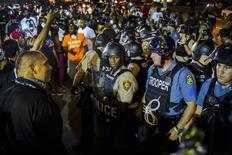 Полиция и протестующие в Фергюсоне, Миссури 10 августа 2015 года. Власти Фергюсона ввели чрезвычайное положение из-за новой волны уличного недовольства, захлестнувшей город в штате Миссури через год после масштабных акций протеста, спровоцированных гибелью чернокожего юноши, которого застрелил белый полицейский. REUTERS/Lucas Jackson