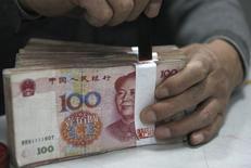 Un empleado sella un fajo de yuanes en una sucursal del Banco Industrial y Comercial de China, en Huaibei, 6 de abril de 2011. China devaluó al yuan el martes después de una serie de datos económicos pobres, guiando la moneda a su punto más bajo en casi tres años. REUTERS/Stringer