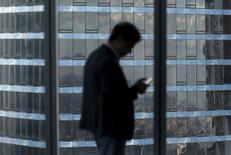 """Мужчина с телефоном в деловом центре Башня Империя в Москва-Сити. 5 августа 2015 года. Инвестиции в коммерческую недвижимость в РФ в первом полугодии 2015 года в годовом выражении снизились на 33 процента до $1,1 миллиарда на фоне снижения экономики, а арендные ставки достигли """"дна"""", говорится в исследовании международного консультанта JLL. REUTERS/Maxim Zmeyev"""