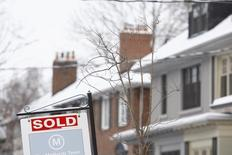 "A ""Sold"" sign hangs in front of a house in Toronto, Ontario in this March 2, 2014 file photo. REUTERS/Hyungwon Kang"