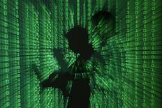 Проекция бинарного кода на силуэт мужчины с ноутбуком. Варшава, 24 июня 2013. Американские прокуроры обвинили группу выходцев из бывшего СССР в получении с помощью кибершпионажа корпоративных пресс-релизов до официальной публикации, позволившем незаконно заработать на инсайде более $30 миллионов. REUTERS/Kacper Pempel