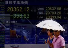 Personas camina junto a un tablero electrónico que muestra el índice Nikkei en Tokio, 12 de agosto de 2015.Las bolsas de Asia subían el jueves impulsadas por un rebote tardío en Wall Street y por las garantías del banco central de China de que no hay base para una depreciación adicional del yuan después de que devaluó a la moneda a principios de esta semana. REUTERS/Thomas Peter