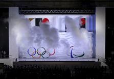 Emblemas dos Jogos Olímpicos e Paralímpicos de Tóquio em 2020 aparecem em meio a fumaça durante evento em Tóquio. 24/07/2015 REUTERS/Yuya Shino