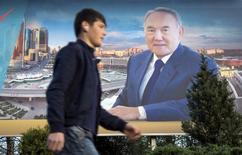 Предвыборный плакат Нурсултана Назарбаева в Алма-Ате 21 апреля 2015 года. Казахстан, вслед за Россией и падающими ценами на нефть, отпустил тенге в свободное плавание и перешел к инфляционному таргетированию. Рынок отреагировал снижением курса тенге на более чем 26 процентов до 255,26 за $1. REUTERS/Shamil Zhumatov