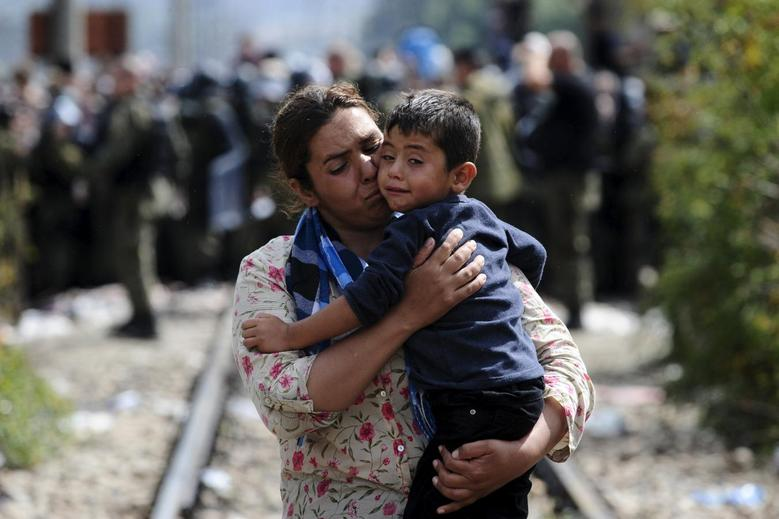 Refugees tear through police lines at Macedonian...