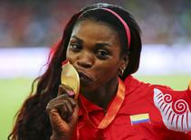 Caterine Ibarguen of Colombia presents her gold medal after winning the women's triple jump event during the 15th IAAF World Championships at the National Stadium in Beijing, China August 24, 2015.    REUTERS/Damir Sagolj