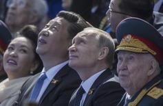 Владимир Путин и Си Цзиньпин смотрят военный парад на Красной площади. Москва, 9 мая 2015 года. Ведущие западные лидеры не появятся на следующей неделе на военном параде в Китае, приуроченном к годовщине завершения Второй мировой войны, оставив председателя Си Цзиньпина в компании Владимира Путина и высокопоставленных представителей Судана, Венесуэлы и Северной Кореи. REUTERS/Host Photo Agency/RIA Novosti