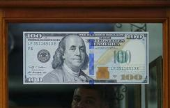 Увеличенная копия 100-долларовой купюры на входе в пункт обмена валюты в Рио-де-Жанейро. 24 августа 2015 года. Доллар подскочил почти на процент к корзине валют и поднялся с семимесячных минимумов к иене и евро после того, как китайский Центробанк сократил процентные ставки и нормы резервирования. REUTERS/Ricardo Moraes