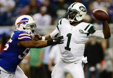 Nov 24, 2014; Detroit, MI, USA; New York Jets quarterback Michael Vick (1) is pressured by Buffalo Bills defensive end Jerry Hughes (55) during the second quarter at Ford Field. Andrew Weber-USA TODAY Sports