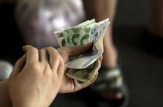 Un cliente sostiene billetes de yuanes mientras paga en un mercado en Beijing, 12 de agosto de 2015. El yuan chino caía el miércoles frente al dólar, después de que el banco central recortó su tasa de interés referencial en 25 puntos básicos y los requisitos de reservas en 50 puntos básicos para la mayoría de los grandes bancos. REUTERS/Jason Lee