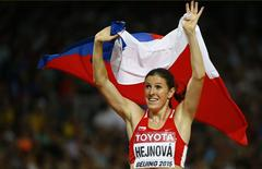 Zuzana Hejnova of the Czech Republic holds her national flag after winning the women's 400 metres hurdles final at the IAAF World Championships at the National Stadium in Beijing, China August 26, 2015.    REUTERS/Damir Sagolj