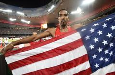 Christian Taylor of the U.S. celebrates with a national flag after winning gold at the men's triple jump final during the 15th IAAF World Championships at the National Stadium in Beijing, China, August 27, 2015.  REUTERS/Dylan Martinez