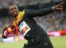 Usain Bolt of Jamaica, gold medal, reacts as he poses on the podium after the men's 200 metres event during the 15th IAAF World Championships at the National Stadium in Beijing, China, August 28, 2015.  REUTERS/Damir Sagolj