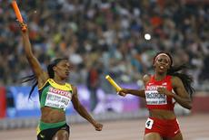 Novlene Williams-Mills of Jamaica (L) crosses the finish line beside Francena McCorory of the U.S. in the women's 4 x 400 metres relay final at the 15th IAAF Championships at the National Stadium in Beijing, China August 30, 2015.  REUTERS/Damir Sagolj