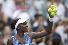 Venus Williams of the U.S. holds signed tennis balls after defeating Monica Puig of Puerto Rico at the U.S. Open Championships tennis tournament in New York, August 31, 2015. REUTERS/Carlo Allegri