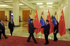 """Le président chinois Xi Jinping (à droite) accueillant son homologue vénézuélien Nicolas Maduro, à Pékin. Le président vénézuélien a annoncé avoir signé avec la Chine un accord portant sur le prêt de cinq milliards de dollars pour augmenter la production pétrolière du pays. Caracas a déjà emprunté 50 milliards de dollars à Pékin dans le cadre d'un accord """"pétrole contre prêts"""" élaboré en 2007, et qui a permis aux entreprises chinoises de gagner des parts de marché au Venezuela. /Photo prise le 1er septembre 2015/REUTERS/Parker Song/Pool"""