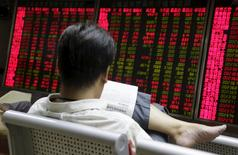 An investor looks at a newspaper in front of an electronic board showing stock information at a brokerage house in Beijing, August 27, 2015. REUTERS/Jason Lee