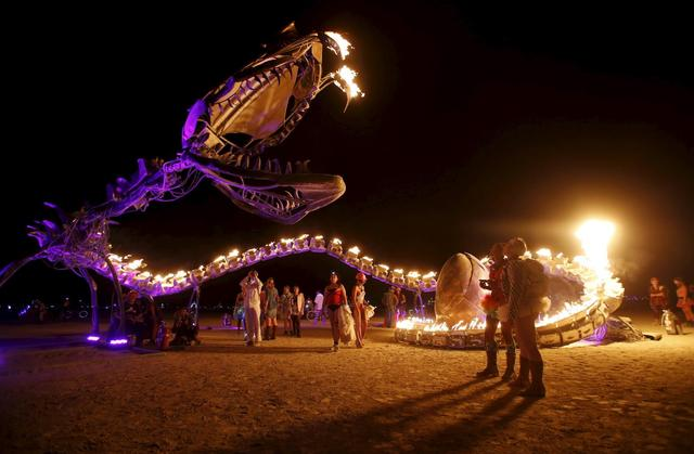 People gather at the art installation Serpent Mother during the Burning Man 2015 ''Carnival of Mirrors'' arts and music festival in the Black Rock Desert of Nevada, September 1, 2015.  REUTERS/Jim Urquhart