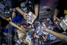 """Customers pick new toys from the upcoming film """"Star Wars: The Force Awakens"""" on """"Force Friday"""" in Hong Kong, China, September 4, 2015. New """"Star Wars"""" toys and other merchandise were released in stores across Hong Kong just after midnight local time during a global rollout of the popular products. REUTERS/Tyrone Siu"""
