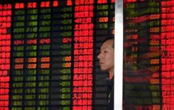 Инвестор в брокерской конторе в Шанхае. 2 сентября 2015 года. Фондовые рынки Китая упали в понедельник после четырехдневных выходных, несмотря на попытки правительства успокоить инвесторов. REUTERS/China Daily