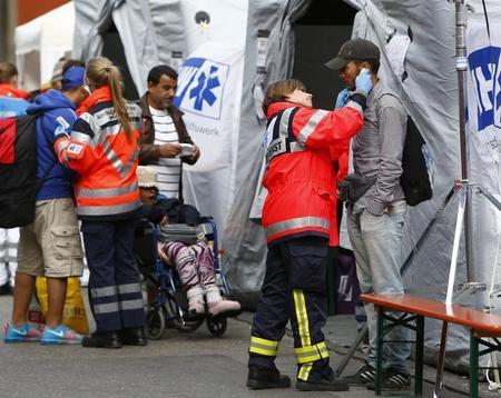 134a6311d لاجئون يتم فحصهم طبيا قبل صعدوهم إلى حافلات بعد وصولهم بالقطار في ميونيخ في  المانيا يوم الاثنين. تصوير: ميكائيلا ريلي - رويترز