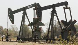 Станки-качалки на нефтяном месторождении ONGC в Ахмедабаде. 1 марта 2012 года. Цены на нефть снижаются за счет избыточного предложения, спада на фондовых рынках Китая, укрепления доллара и данных о занятости в США. REUTERS/Amit Dave