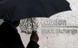 A man shelters under an umbrella as he walks past the London Stock Exchange in London, Britain, in this August 24, 2015 file photo. REUTERS/Suzanne Plunkett/Files